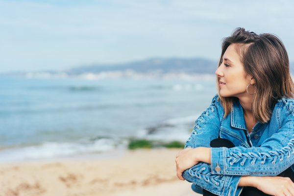 Thoughtful young woman gazing out over the sea as she sits in a denim jacket above a sandy beach on a misty day